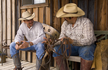 The cowboy life in the USA West as cowboys relax and talk on old porch at the ranch