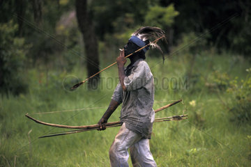 Brazil. Guarani-Kaiowas indigenous people. Acculturated brazilian indian smoking cigarettes and wearing clothes. Mix of traditional culture ( native weapons  like arrows ) and influence of the white culture.
