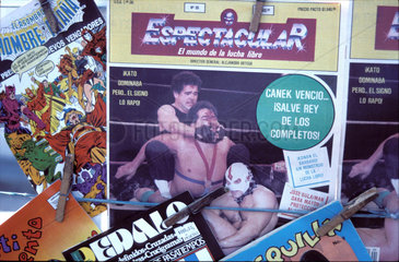 Mexico; magazines at a kiosk  one showing a match of lucha libre  a local popular form of wrestling