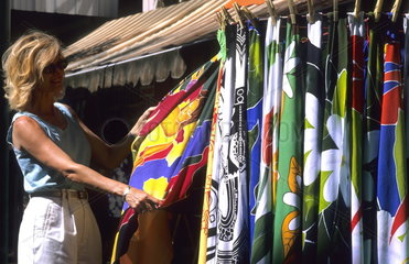 Tourist woman shopping for colorful fabric dress in Tahiti capital of Plage de Surf Papeete in French Polynesia