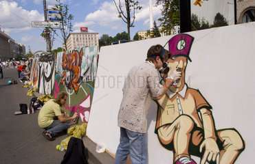 Artists spray painting artwork at street festival of closing the main street Khrechatk Strret with people in Kiev Ukraine