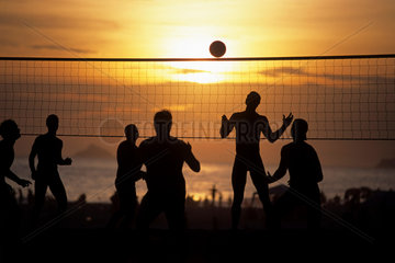 Men recreating on Ipanema beach  Rio de Janeiro  Brazil. Sports  futevolei (or footvolley). This is the beach volleyball game played on the beach using only feet  chest and head to hit the ball. Action  athletics  athletes  energetic  competitions  disput