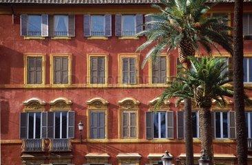 Façade ocre du centre ville avec palmiers.