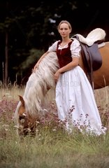 Young woman romantic dress held almost a horse palomino