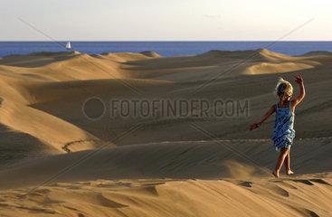 Gran Canaria  Playa del Ingles  Oasis de maspalomas  a girl walking over the ridges of the sand dunes  a sailingboat on the sea