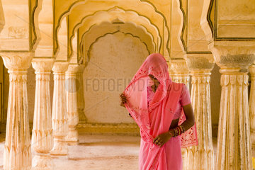 Beautiful graphic arches with colorful Hindu gentle woman posed at Amber Fort temple in Rajasthan Jaipur India