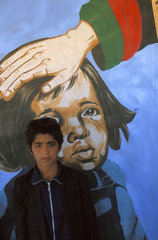 Kabul  portrait of a boy in front of a painting which claims the government is taking care of the Afghan children