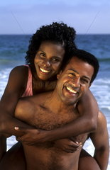 Attractive black african american couple in swim suits relaxing on the beach on holiday and enjoying the togetherness and caring