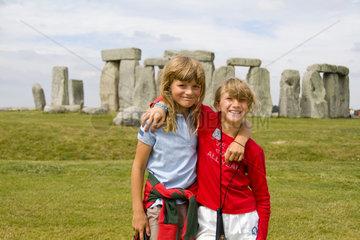 Two young girls hugging and happy in front of the world famous Stonehenge monument in England Great Britian
