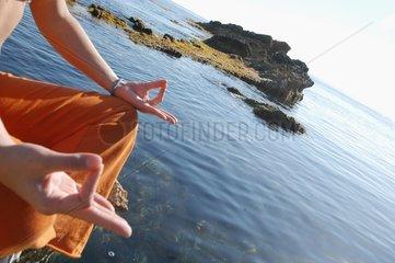 Mixed race woman in Lotus posture facing the sea Ibiza