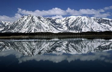 Reflections of Grand Teton snowy mountains in a lake USA