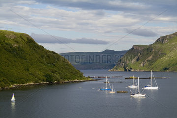 Beautiful port and sailboats with reflections in small tourist village of Portree in Isle of Skye Western Highlands Scotland
