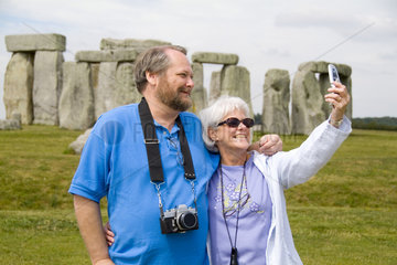 Middle aged couple taking photo in front of the world famous Stonehenge monument in England Great Britian