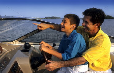 Hispanic father and son sharing the fun of boating and driving the boat together laughing and relaxing a fathers love