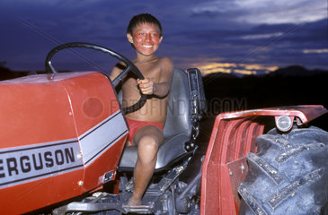 Yanomami child plays with Brazilian Army tractor  Surucucus  Roraima  Amazon rainforest  Brazil. Ianomami indigenous people  acculturated indian  cultural degradation  cultural influence. smile boy smiling Ingenuousness  purity  innocence