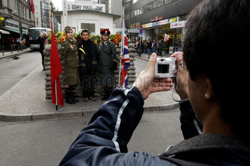 Berlin  a Russian and a British soldier posing with a tourist at checkpoint Charlie in the Friedrichstrasse