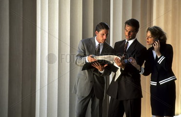 Professional business people discussing business with newspaper near pillars that look like Wall Street