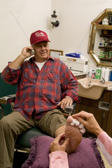 Small middle town barber shop in America trucker type man getting a pedicure while talking on cell phone odd situation humorous
