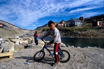 Inuit boy riding cycle Ittoqqottoormiit village Greenland