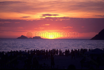 People admire sunset at Ipanema beach  Rio de Janeiro  Brazil. Audience  travel  tourism  crowd.