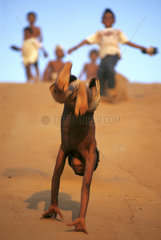 Natal  Northeastern Brazil. Children play in the dunes. somersault  handspring  dark-skinned boy upside down  action  active  activities  activity  fast  quick  speedy  rapid