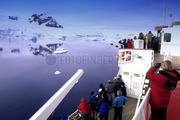 Tourists taking whale watching cruise among icebergs on icebreaker ship in Antarctica