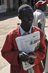 Newspapers seller after an annular solar eclipse Kenya