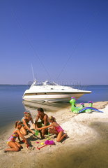 Family playing on shore after boating together to relax