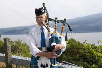 Colorful outfit and personality of bag pipe player at the Loch Ness area near Drumnadrochit home of the Loch Ness Monster Nessie in the Scotish Highland