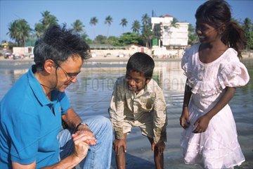 Jeux de mains entre un touriste et des enfants mendiant