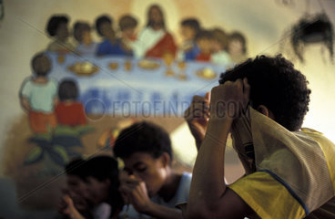 Street children  Rio de Janeiro  Brazil. Children under risky situation  involved with small crimes  afraid of showing their faces  living in a social institution. Dinner time  meal  supper  Catholicism  Jesus Christ  fear.