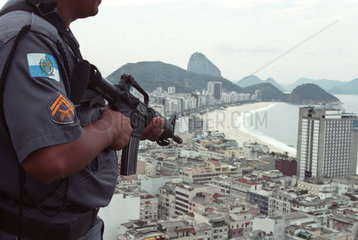 Policeman aims machine-gun to Copacabana quarter. Drugs traffic war in Rio de Janeiro  Brazil. Violence. Sugar Loaf in the background.