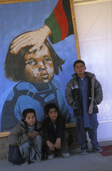 Kabul  portrait of a boys in front of a painting which claims the government is taking care of the Afghan children