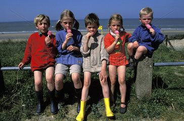 Group of children eating an icescream near the beach