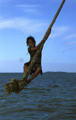 Tonga  a girl swinging on a rope above the pacific ocean
