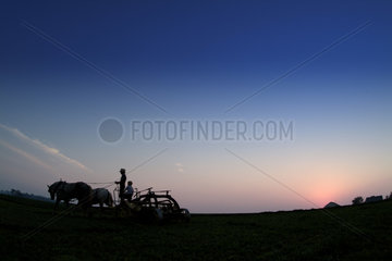 Old Amish Farm with man on plow working fields Intercourse Pennsylvania
