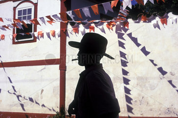 Festa Junina ( June party or Saint Johns Party ) in Caruaru city  Pernambuco state  Brazil. Countryman smoking straw-cigarette. Colorful flags  street decoration  popular culture  popular party  South America  Latin America