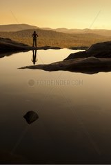 Woman and golden reflections at sunset in the Kakadu NP