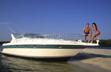 Couple relaxing on graphic boat on shore to do the good life in upscale boat