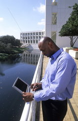Black african american man outdoors communicating with computer in business situation