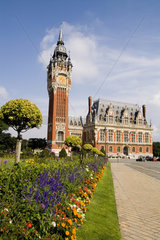 Colorful flowers in sunshine of beautiful Hotel de Ville architecture in small Frence village of Calais France