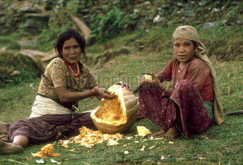 NEPAL : Pokhara province. Gurung mother and daughter with a large pumkin in a mountain village in the Annapurna region..