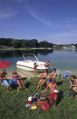 Many couples playing on grass after boating and relaxing