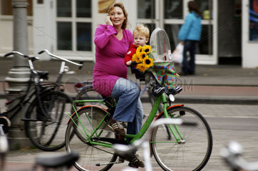 Amsterdam  a young pregnant mother on her bicycle with flowers  her toddler boy and her cell phone
