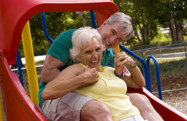 Senior retired couple having fun at playground outside with slide