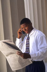 Black african american male business man talking on cell phone and checking newspsper stock prices to communicate with other office