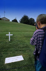 A young boy takes picture of the famous Bobby Kennedy grave in Washington DC in the USA