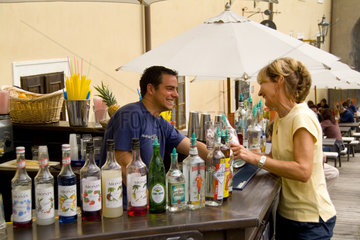 Tourist having a talk and drink with street bartender vendor of tourist city of Cesky Krumlov in Czech Republic