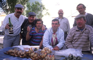 Tough and rough old fishermen relaxing at a bar in the village of Olmao in the Algarve in Southern Portugal in Europe