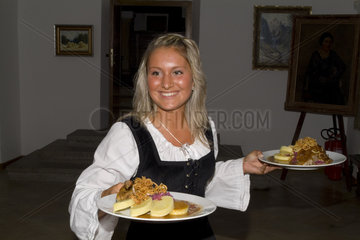 Waitress bringing plates of duck food in Cesky Krumlov Czech Republic